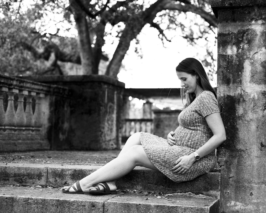 Black and white photo of a glowing pregnant woman sitting at Entrance Park in Coral Gables, Florida. Photographed by Savannah Maternity Photographer, Kristen M. Brown, Samba to the Sea Photography.