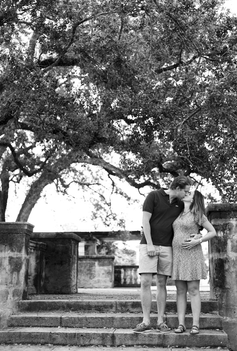 Black and white photo of couple kissing at Entrance Park in Coral Gables, Florida. Photographed by Savannah Maternity Photographer, Kristen M. Brown, Samba to the Sea Photography.