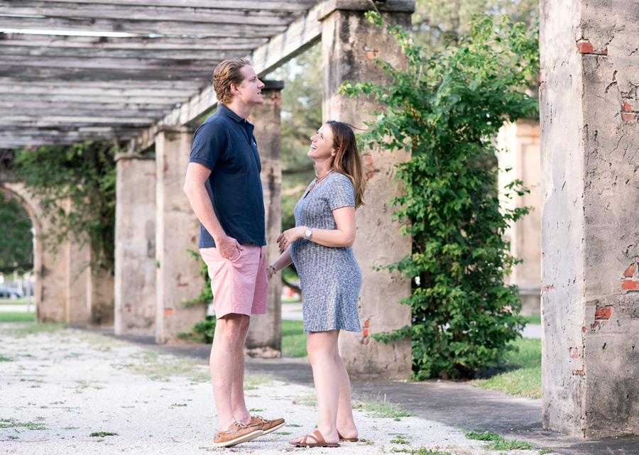 Young couple laughing during maternity photos at Entrance Park in Coral Gables, Florida. Photographed by Savannah Maternity Photographer, Kristen M. Brown, Samba to the Sea Photography.