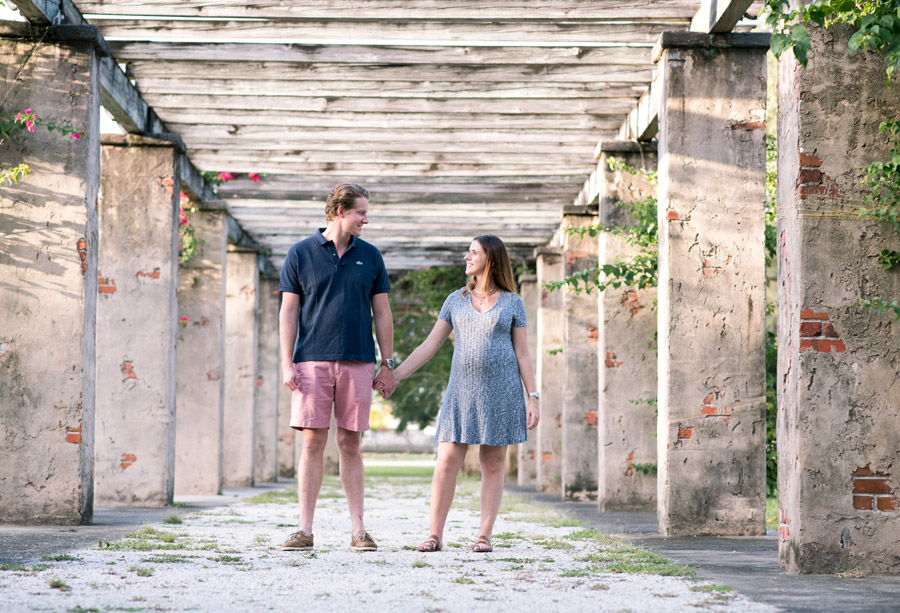 Couple holding hands during maternity photos at Entrance Park in Coral Gables, Florida. Photographed by Savannah Maternity Photographer, Kristen M. Brown, Samba to the Sea Photography.