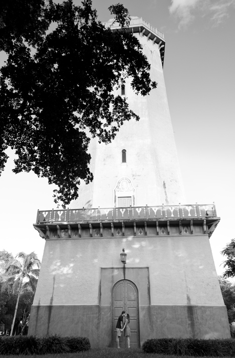 Black and white photo of couple standing in front of the Alhambra Water Tower in Coral Gables, Florida. Photographed by Savannah Maternity Photographer, Kristen M. Brown, Samba to the Sea Photography.