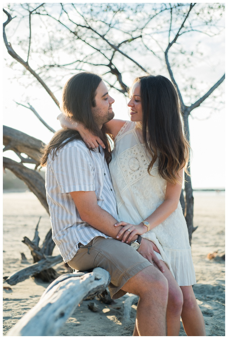 Newly engaged couple sharing a moment during engagement photos on the beach in Tamarindo. Costa Rica. Girlfriend is wearing an boho chic dress from Free People. Photographed by Kristen M. Brown, Samba to the Sea Photography.