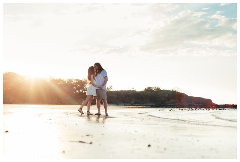 Couple kissing on the beach with the sun streaming over the hill in Tamarindo, Costa Rica. Girlfriend is wearing an boho chic dress from Free People. Photographed by Kristen M. Brown, Samba to the Sea Photography.