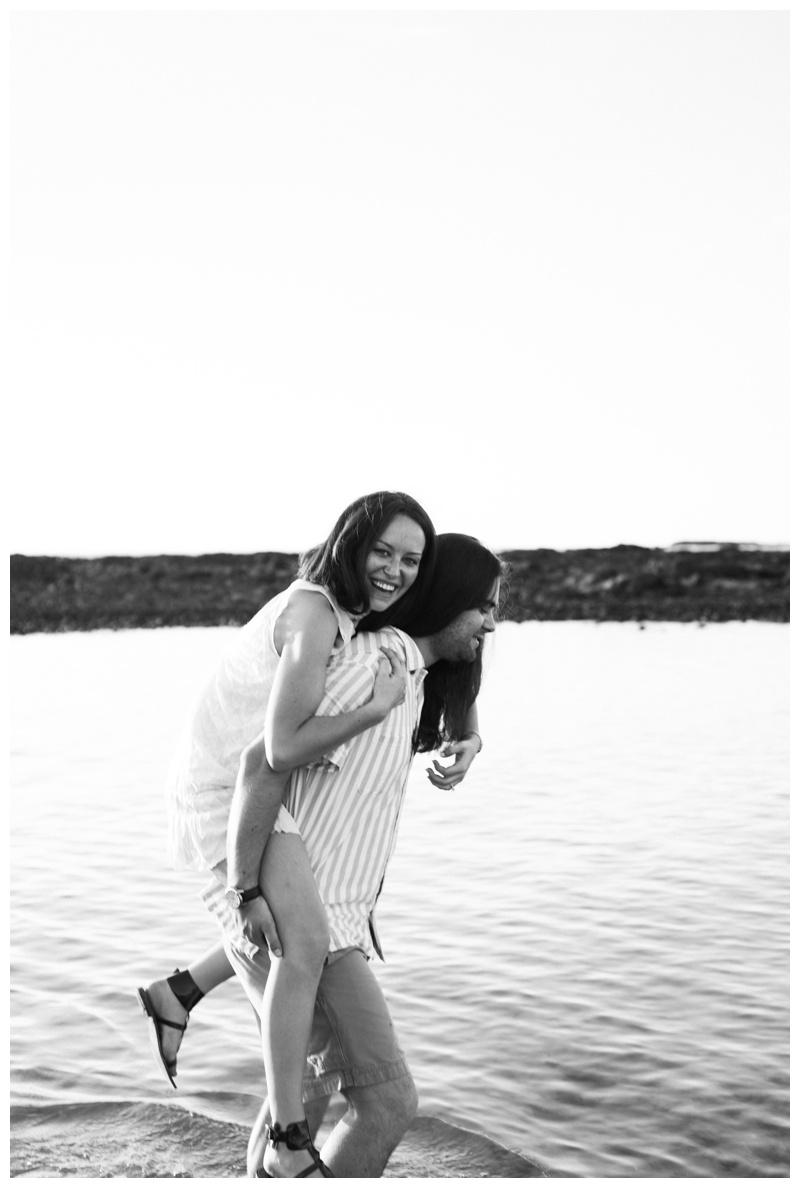 Fiance giving his girlfriend a piggy back ride during engagement photos in Costa Rica. Girlfriend is wearing an boho chic dress from Free People. Photographed by Kristen M. Brown, Samba to the Sea Photography.