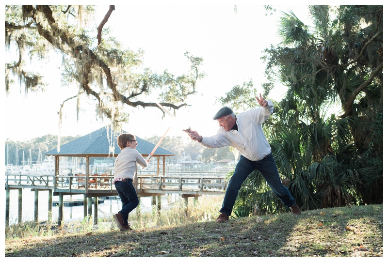 Grandfather and grandson in a sword fight during family photos on Bluff Drive in Isle of Hope, GA. Photographed by Kristen M. Brown, Samba to the Sea Photography.
