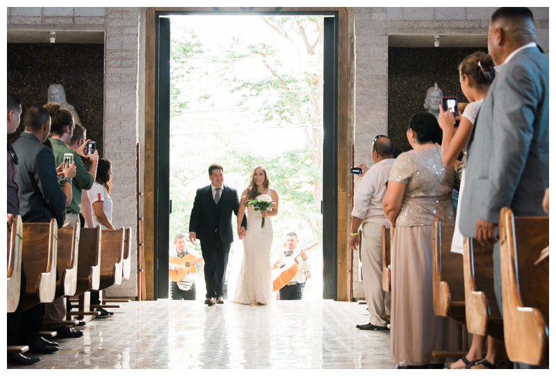 Bride walking down the aisle with her father at Santa Maria Church in Tamarindo, Costa Rica. Photographed by Kristen M. Brown, Samba to the Sea Photography.