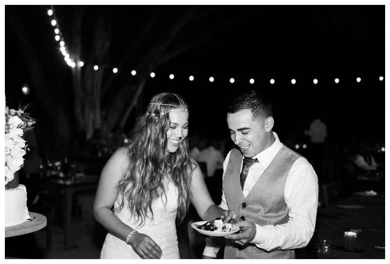 Black and white photo of bride and groom laughing during their cake cutting at Pangas Beach Club in Tamarindo, Costa Rica. Photographed by Kristen M. Brown, Samba to the Sea Photography.
