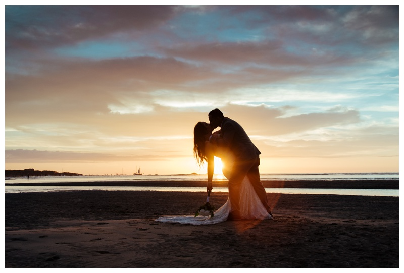Groom dipping his bride at sunset on the beach in Tamarindo, Costa Rica.