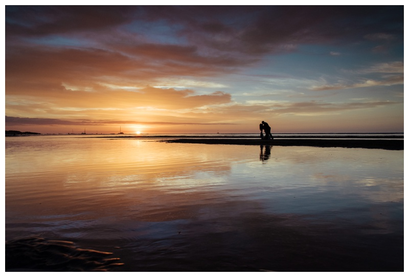Silhouette Of Groom Dipping His Bride During A Breathtaking Vibrant Sunset On The Beach In