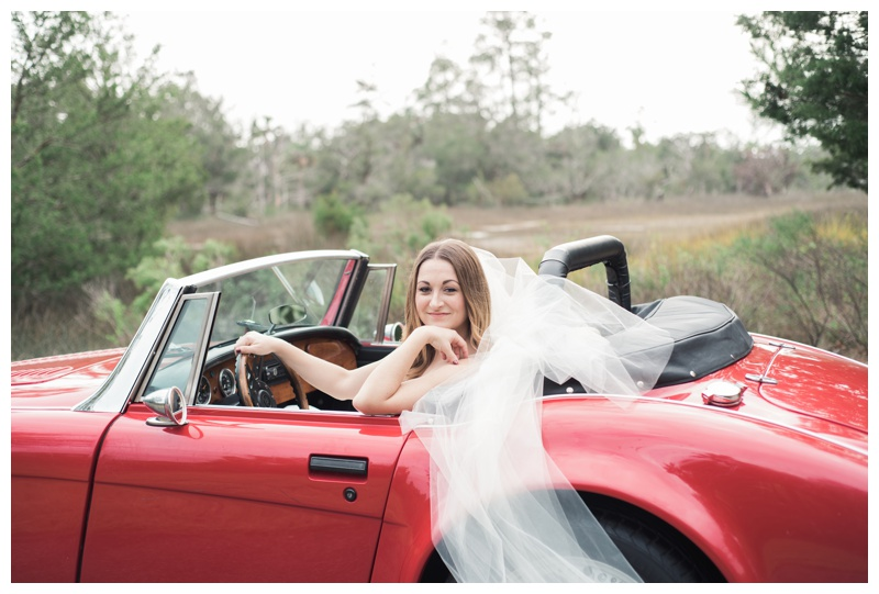 Bridal portraits in a red classic convertible Austin Healey. Bride is wearing a gorgeous dress by Maggie Sottero Designs and veil by Adele Amelia Bridal, available at Ivory & Beau Bridal Boutique in Savannah, GA. Photographed by Kristen M. Brown, Samba to the Sea Photography.