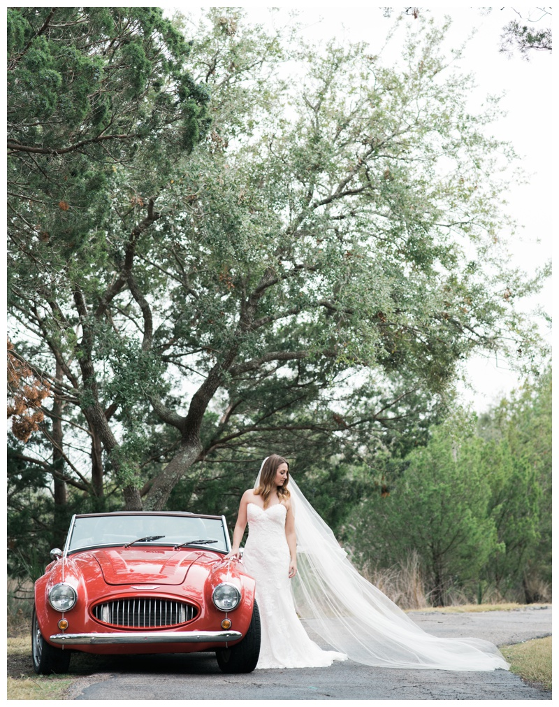 Stunning classic red convertible car bridal portrait in Savannah, Georgia. Bride is wearing a gorgeous dress by Maggie Sottero Designs and veil by Adele Amelia Bridal, available at Ivory & Beau Bridal Boutique in Savannah, GA. Photographed by Kristen M. Brown, Samba to the Sea Photography.