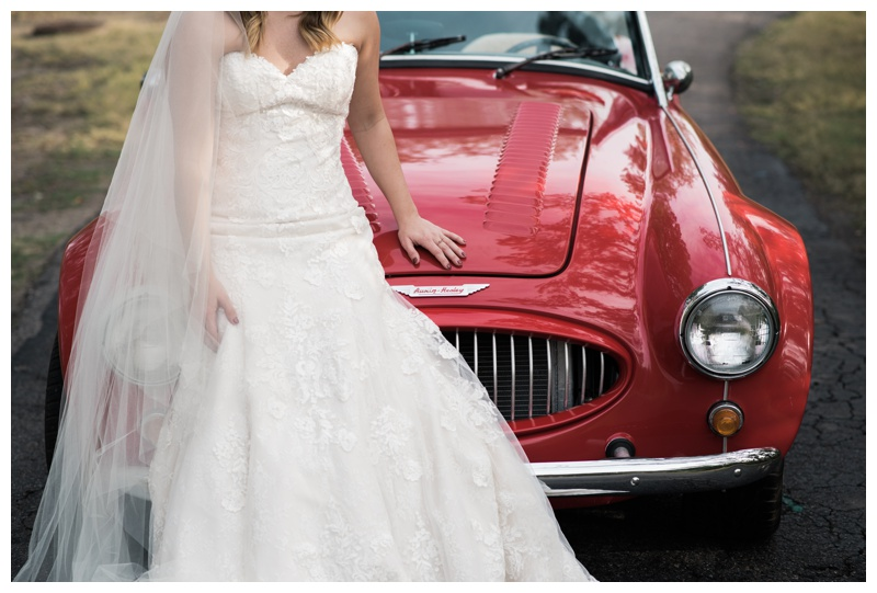 Bride sitting on the hood of a red classic convertible Austin Healey in Savannah, Georgia. Bride is wearing a gorgeous dress by Maggie Sottero Designs and veil by Adele Amelia Bridal, available at Ivory & Beau Bridal Boutique in Savannah, GA. Photographed by Kristen M. Brown, Samba to the Sea Photography.