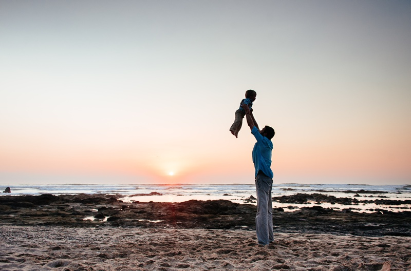 Father tossing his young son on the beach during sunset in Playa Langosta, Costa Rica. Photographed by Kristen M. Brown, Samba to the Sea Photography.
