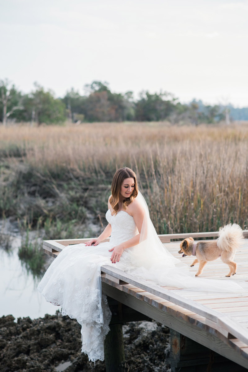 Marsh bridal portraits in Savannah, Georgia on Skidaway Island with Ivory and Beau Bridal Boutique. Model is wearing a Maggie Sottero Designs wedding dress and holding her cute dog. Photographed by Kristen M. Brown, Samba to the Sea Photography.