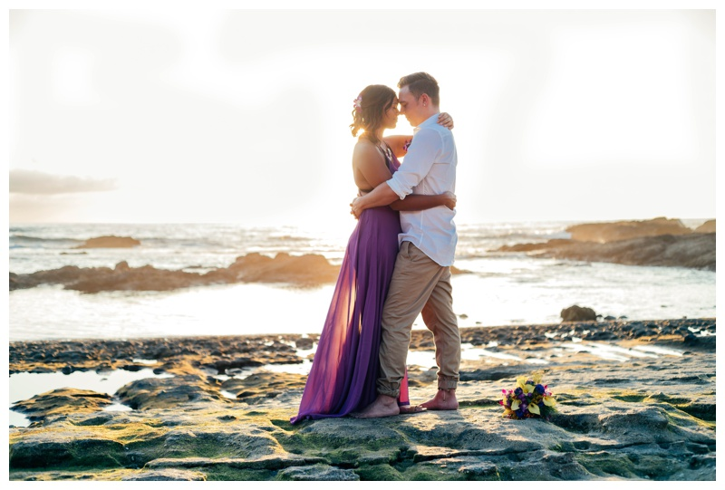 Bride and groom embracing on the beach during golden hour in Costa Rica. Bride is wearing a purple wedding dress. Photographed by Kristen M. Brown, Samba to the Sea Photography.