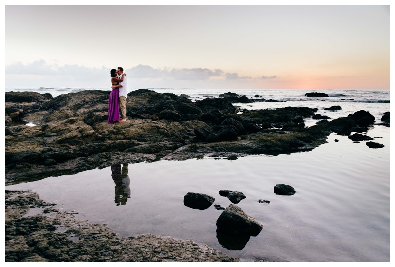 Bride and groom embracing on the beach during sunset in Costa Rica. Bride is wearing a purple wedding dress. Photographed by Kristen M. Brown, Samba to the Sea Photography.