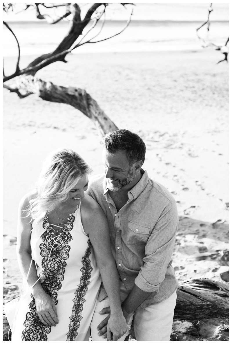 Black and white portrait of husband and wife laughing on the beach in Playa Hermosa, Costa Rica. Photographed by Kristen M. Brown, Samba to the Sea Photography.