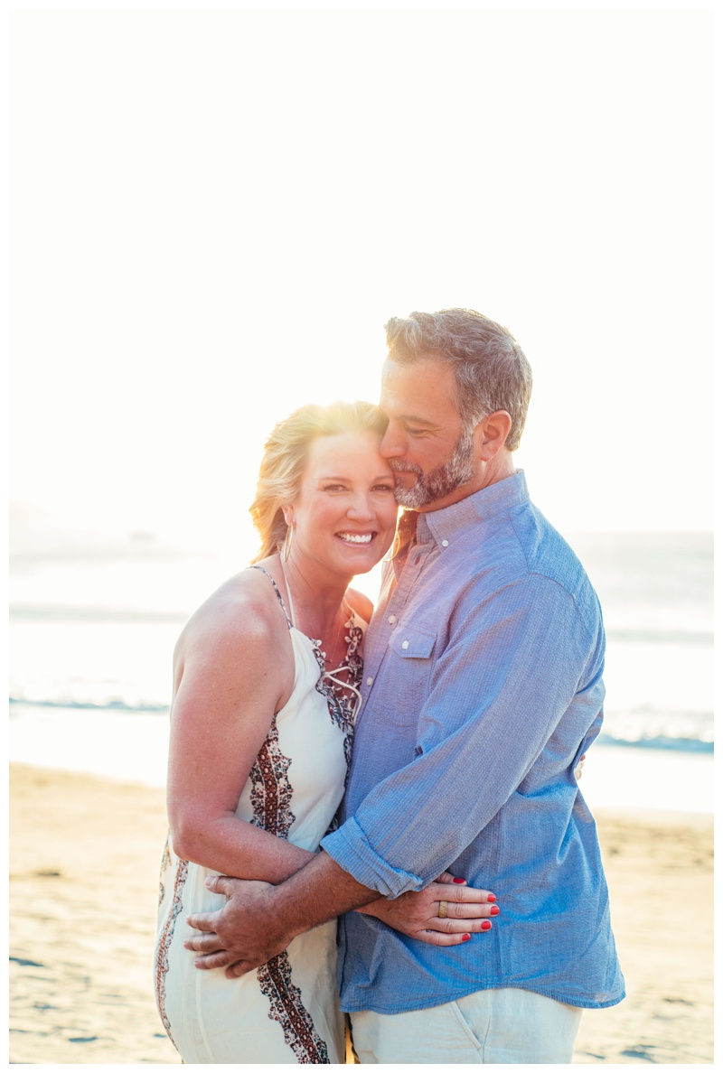 Portrait of husband hugging his wife during golden hour in Playa Hermosa, Costa Rica. Photographed by Kristen M. Brown, Samba to the Sea Photography.