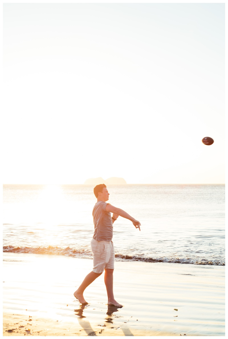 Teenage boy throwing a football on the beach in Playa Hermosa, Costa Rica. Photographed by Kristen M. Brown, Samba to the Sea Photography.