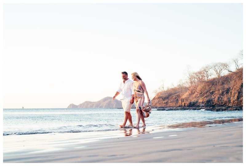 Couple walking on the beach holding hands during sunset in Playa Hermosa, Costa Rica. Photographed by Kristen M. Brown, Samba to the Sea Photography.