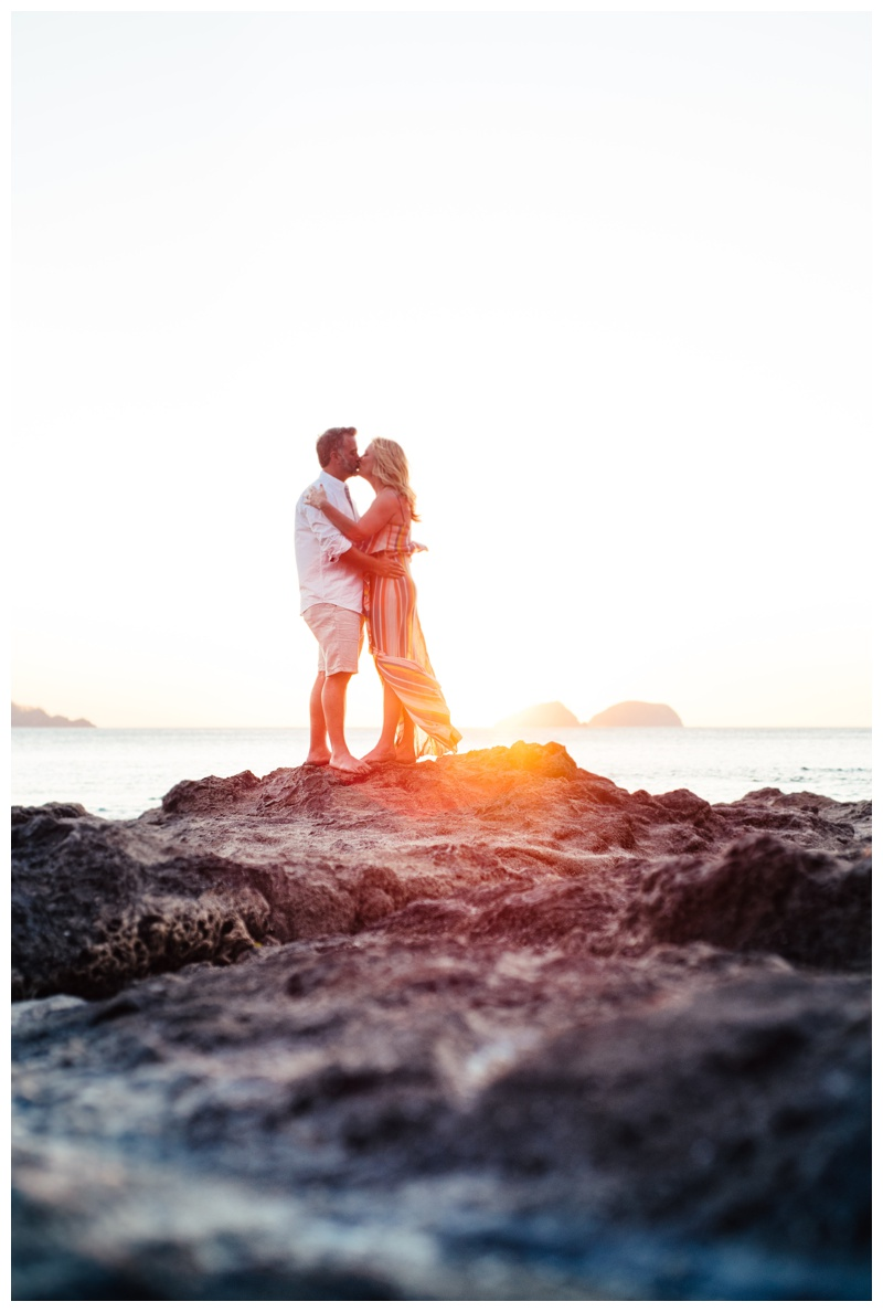 Husband and wife kissing on the low tide rocks during golden hour in Playa Hermosa, Costa Rica. Photographed by Kristen M. Brown, Samba to the Sea Photography.