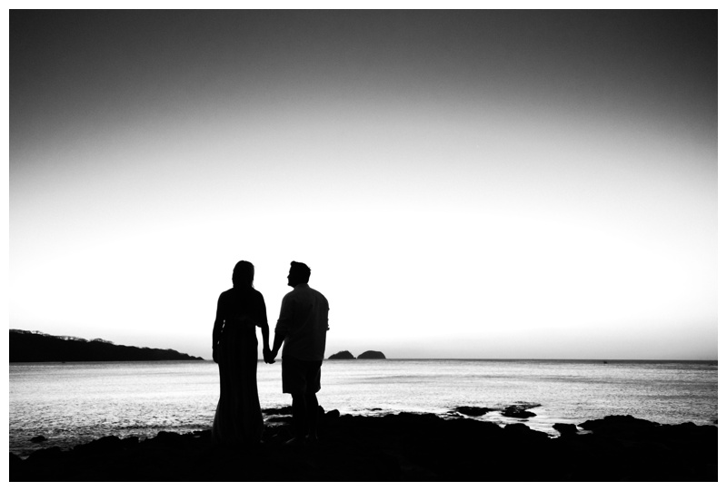 Black and white silhouette of couple holding hands on the beach in Playa Hermosa, Costa Rica. Photographed by Kristen M. Brown, Samba to the Sea Photography.