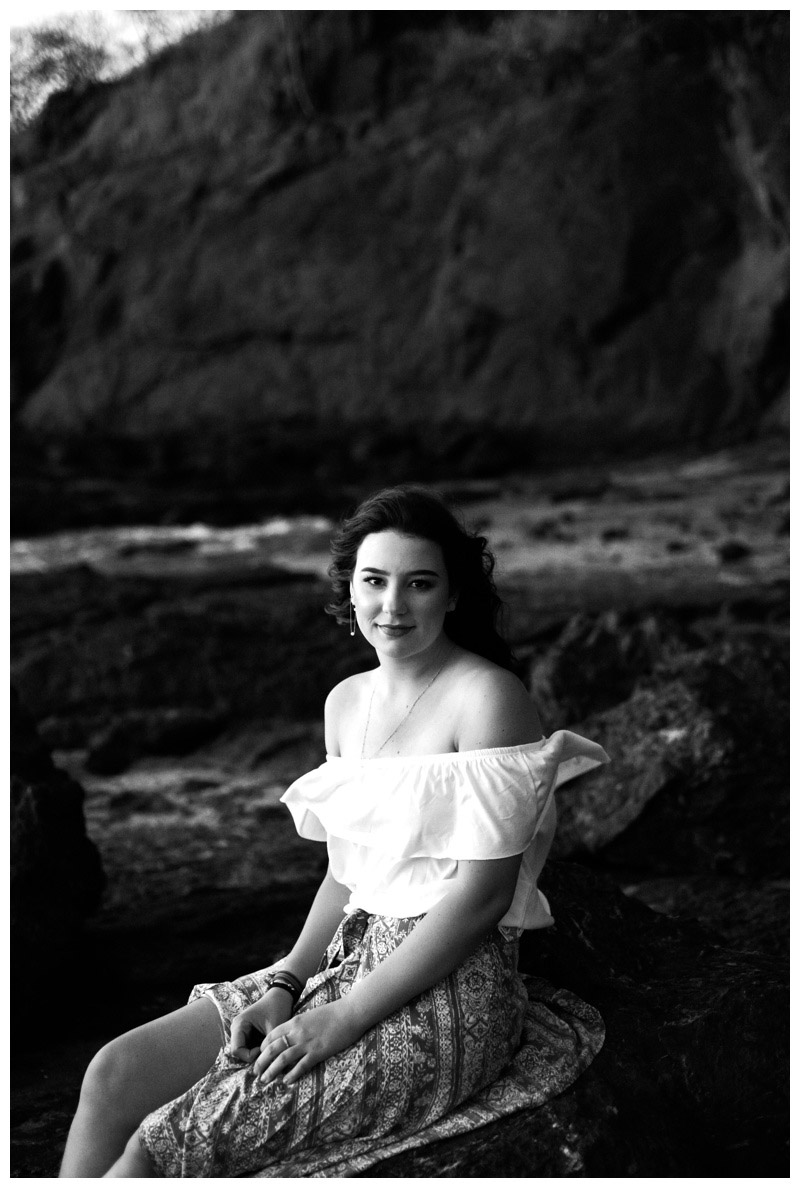 Black and white portrait of young woman on the rocks in Playa Hermosa, Costa Rica. Photographed by Kristen M. Brown, Samba to the Sea Photography.