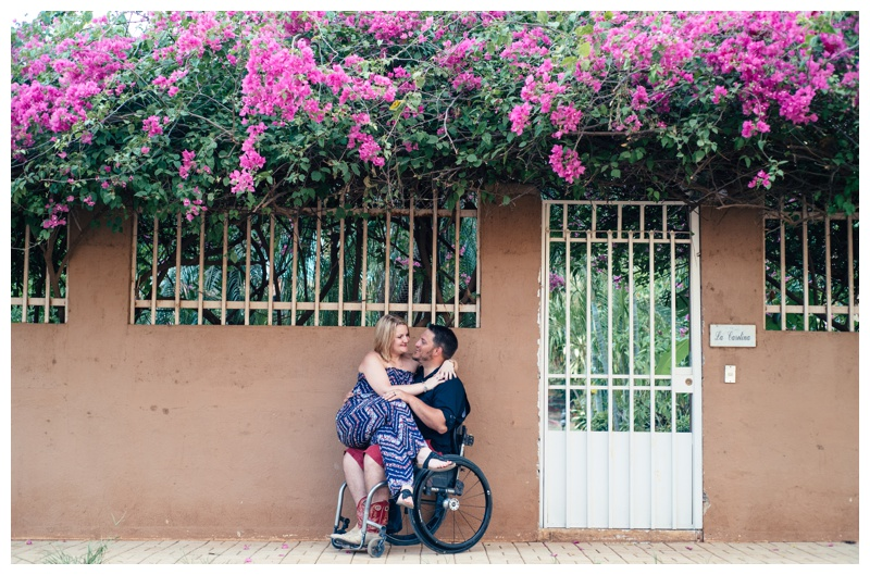 Wife sitting on her husband's lap in front of a gorgeous, magenta pink borganvillea bush in Tamarindo, Costa Rica. Photographed by Kristen M. Brown, Samba to the Sea Photography.