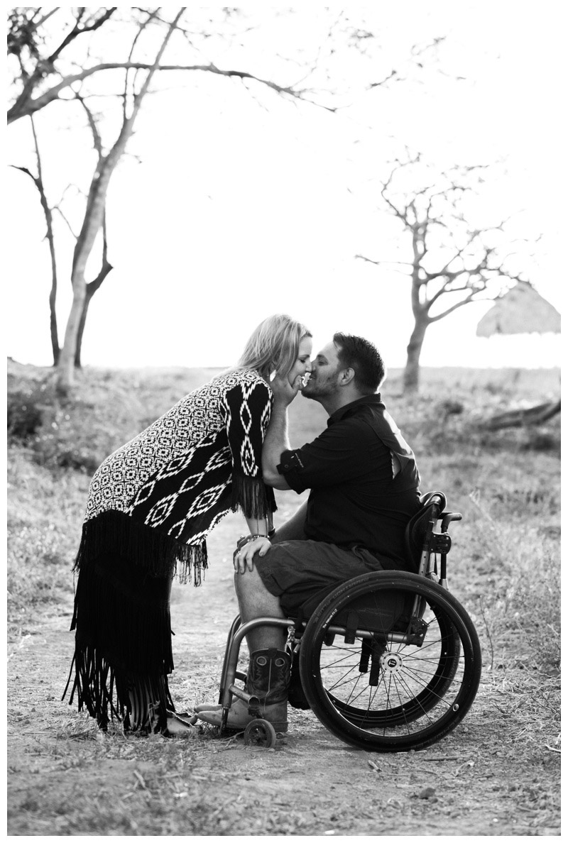 Black and white image of husband kissing his wife at the lookout in Tamarindo, Costa Rica. Photographed by Kristen M. Brown, Samba to the Sea Photography.