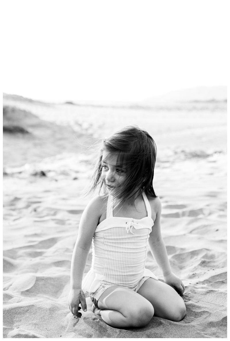 Black and white image of young girl on the beach in Tamarindo, Costa Rica. Photographed by Kristen M. Brown, Samba to the Sea Photography.