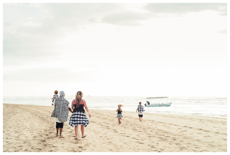 Family walking on the beach towards a Panga boat in Tamarindo, Costa Rica. Photographed by Kristen M. Brown, Samba to the Sea Photography.