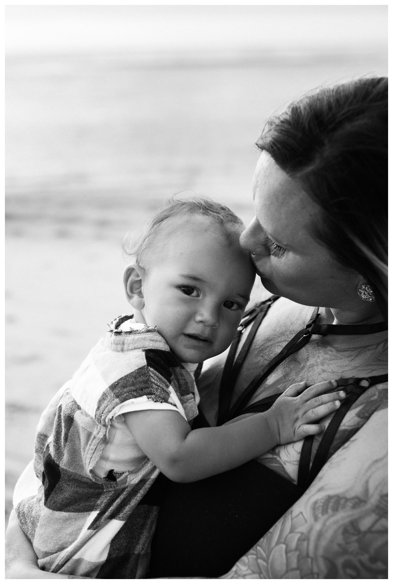 Black and white photo of mom kissing her baby boy during family photos in Tamarindo, Costa Rica. Photographed by Kristen M. Brown, Samba to the Sea Photography.