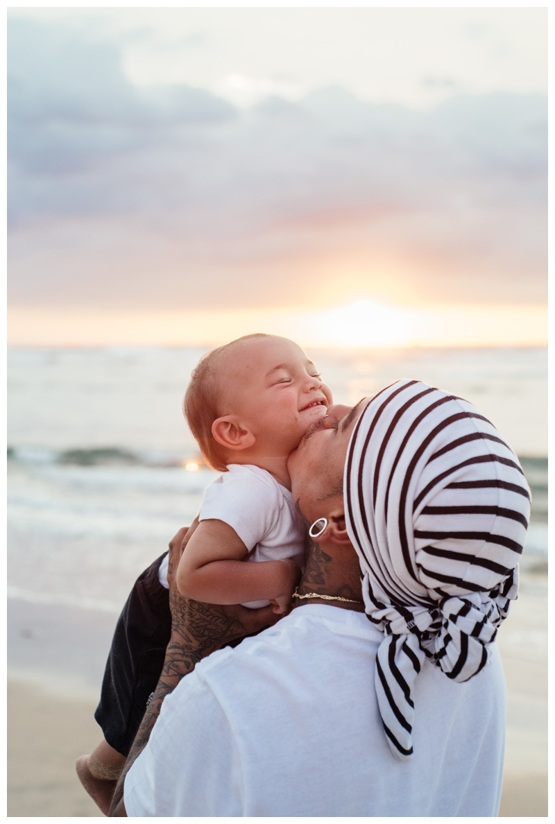 Father kissing his baby boy on the beach in Tamarindo, Costa Rica during a gorgeous sunset. Photographed by Kristen M. Brown, Samba to the Sea Photography.