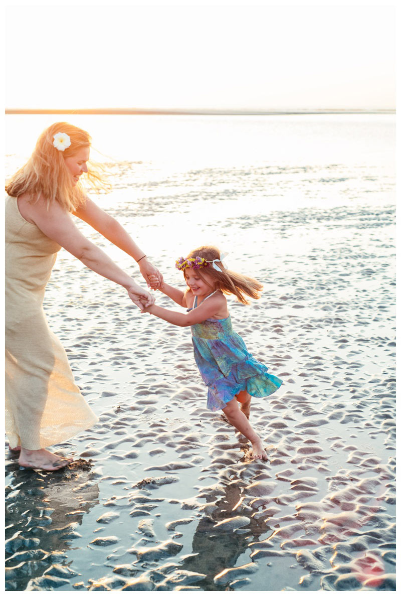 Mom and daughter spinning on the beach during golden hour in Tamarindo, Costa Rica. Photographed by Kristen M. Brown, Samba to the Sea Photography.