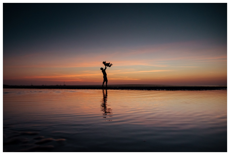 Silhouette of father throwing his daughter into the air during a gorgeous sunset in Tamarindo, Costa Rica. Photographed by Kristen M. Brown, Samba to the Sea Photography.