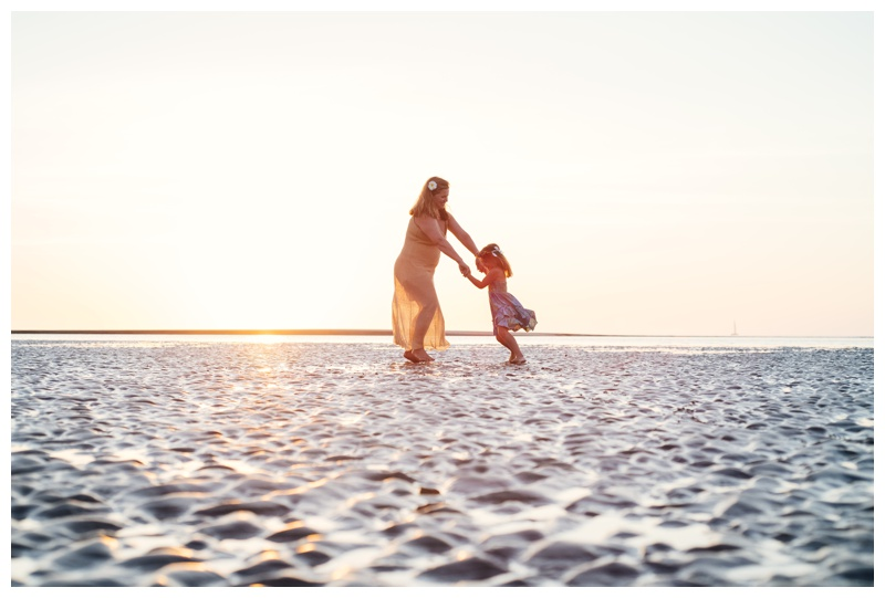 Mother and daughter spinning on the beach in Tamarindo, Costa Rica during golden hour. Photographed by Kristen M. Brown, Samba to the Sea Photography.