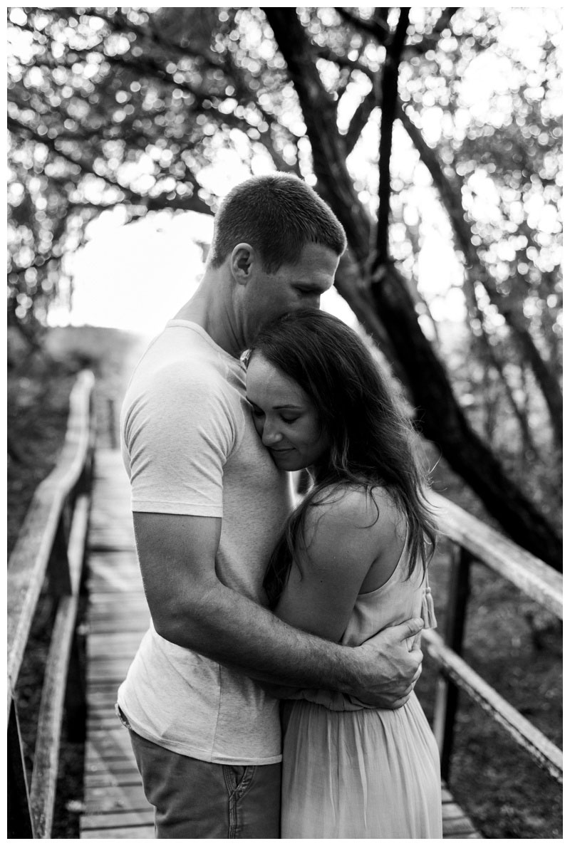 Black and white photo of couple embracing in a hidden beach path in Tamarindo, Costa Rica. Photographed by Kristen M. Brown, Samba to the Sea Photography.