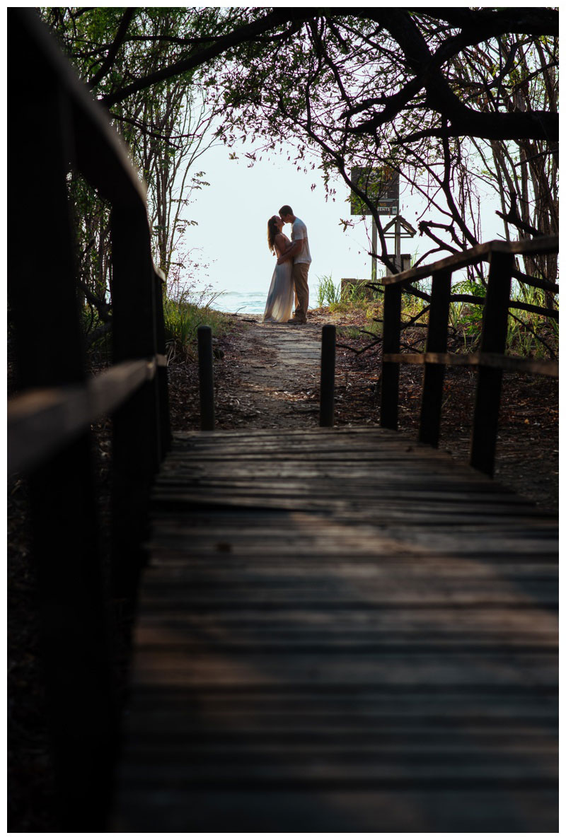 Couple kissing in a hidden beach path in Tamarindo, Costa Rica. Photographed by Kristen M. Brown, Samba to the Sea Photography.