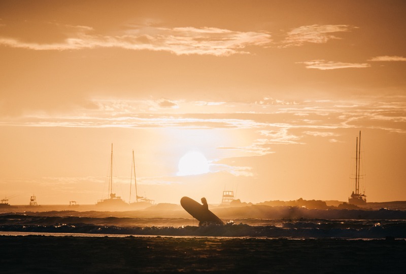 Female surfer walking out of the ocean with her surfboard during a golden sunset in Tamarindo, Costa Rica. 5 Beach Photography Tips, Photographed by Kristen M. Brown, Samba to the Sea Photography.