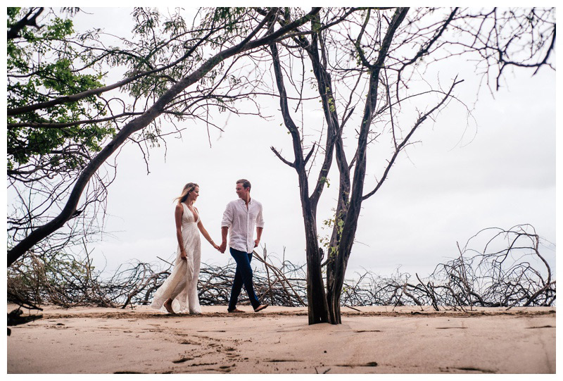 Husband and wife walking on a hidden beach path in Tamarindo, Costa Rica. Photographed by Kristen M. Brown, Samba to the Sea Photography.