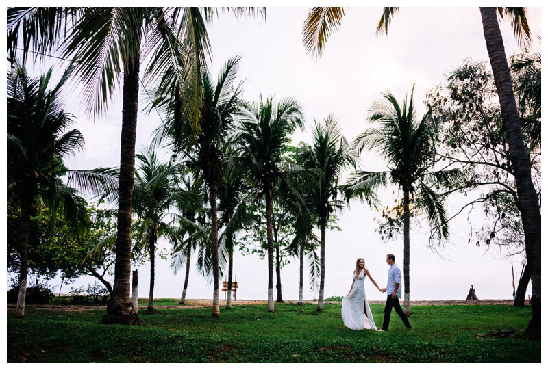 Wife leading her husband through a palm tree grove in Tamarindo, Costa Rica. Photographed by Kristen M. Brown, Samba to the Sea Photography.