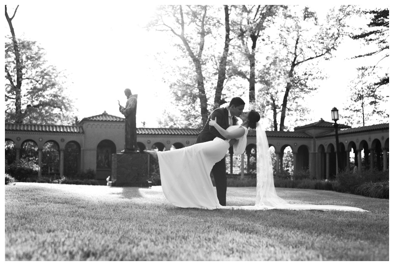 Black and white photo of groom dipping his bride in the gardens of St. Francis monastery. Photographed by Kristen M. Brown, Samba to the Sea Photography.