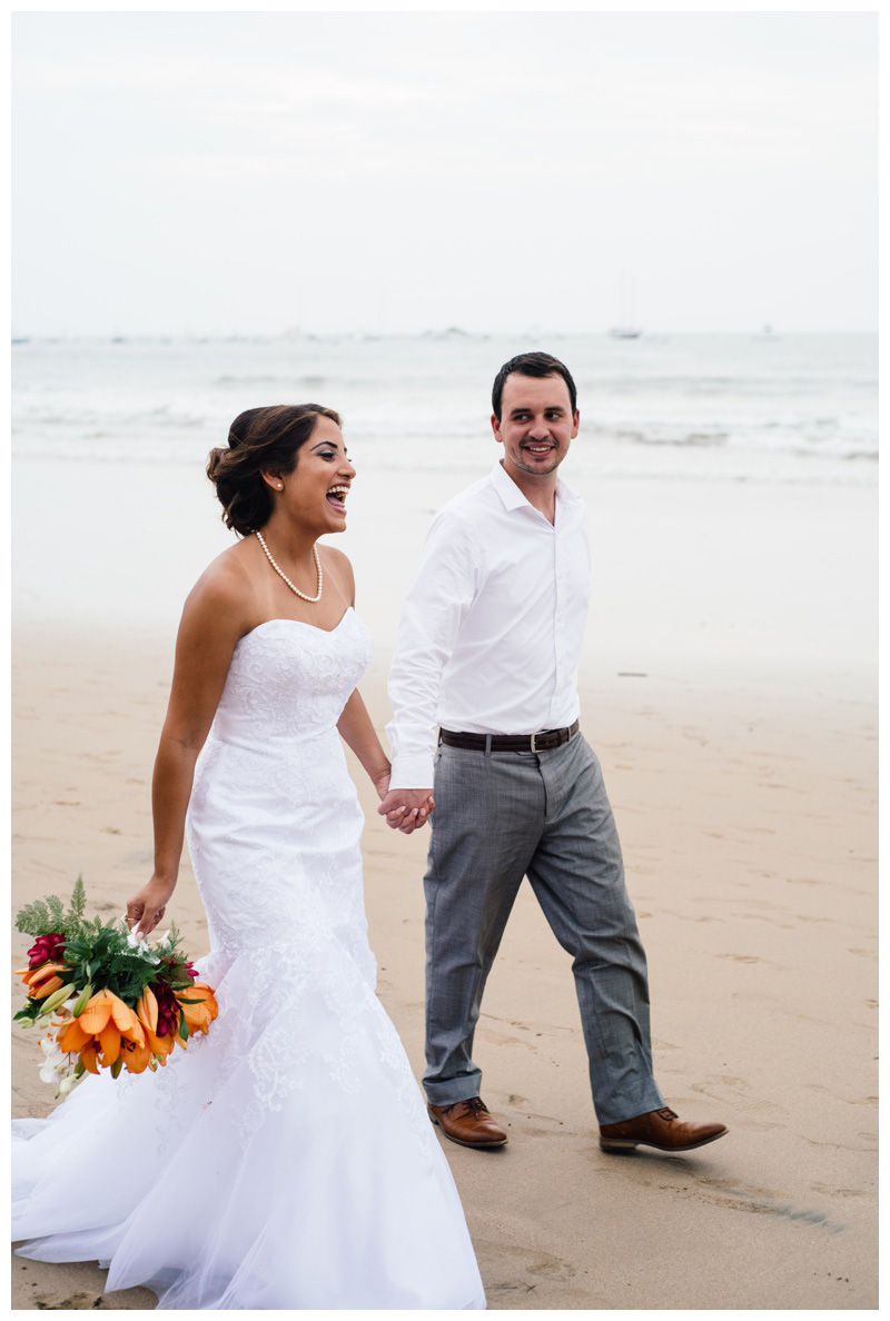 Bride and groom walking on the beach in Tamarindo, Costa Rica. Photographed by Kristen M. Brown, Samba to the Sea Photography. Photographed by Kristen M. Brown, Samba to the Sea Photography.