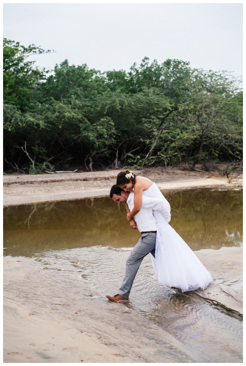 Groom giving his bride a piggy back ride over a beach stream in Costa Rica. Photographed by Kristen M. Brown, Samba to the Sea Photography.