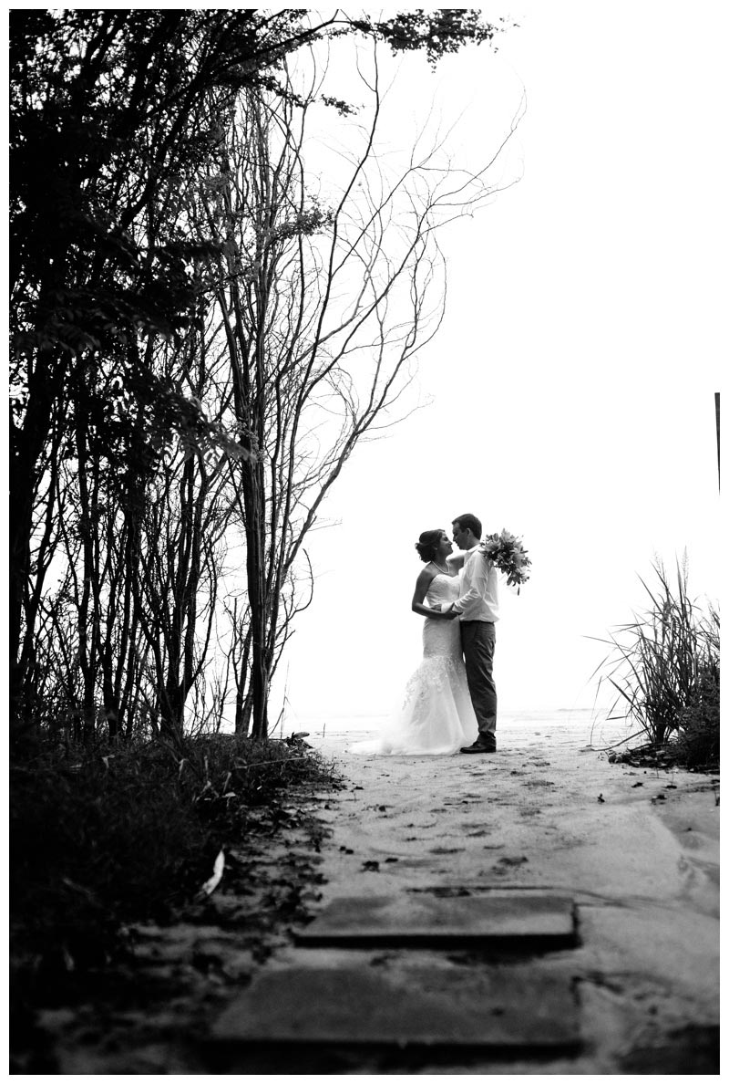 Black and white photo of bride and groom at the end of a secret beach path in Tamarindo, Costa Rica. Photographed by Kristen M. Brown, Samba to the Sea Photography.