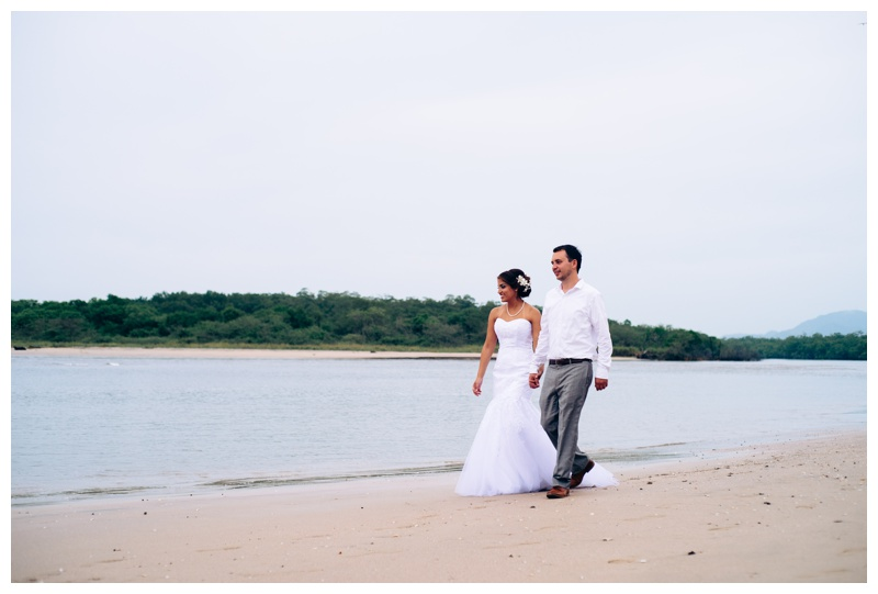 Bride and groom walking on the beach in Tamarindo, Costa Rica. Photographed by Kristen M. Brown, Samba to the Sea Photography.