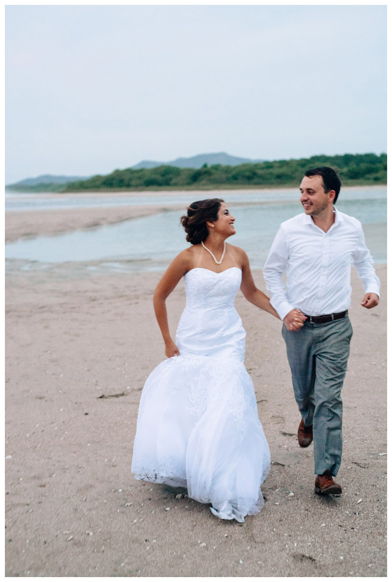 Bride and groom running on the beach in Tamarindo. Photographed by Kristen M. Brown, Samba to the Sea Photography.