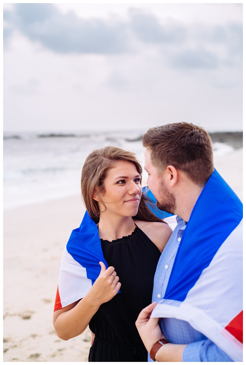 Couple embracing holding the Costa Rican flag on the beach in Costa Rica. Photographed by Kristen M. Brown, Samba to the Sea Photography.