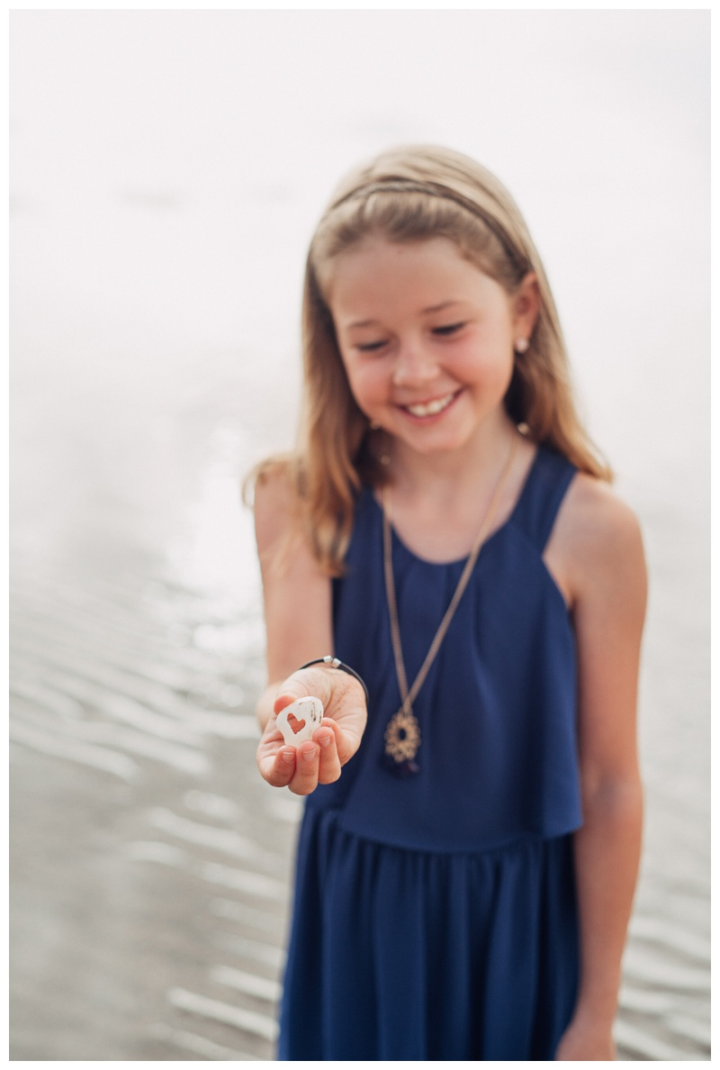 Young girl holding a shell with a cut out heart in Tamarindo Costa Rica. Photographed by Kristen M. Brown, Samba to the Sea Photography.