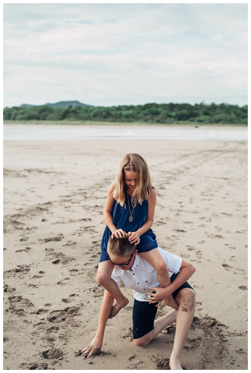 Brother giving his little sister a piggy back ride on the beach in Tamarindo Costa Rica. Photographed by Kristen M. Brown, Samba to the Sea Photography.